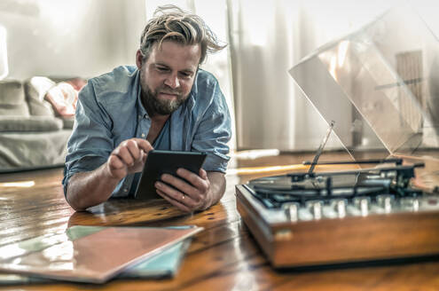 Man lying on the floor at home with tablet and record player - RIBF01033