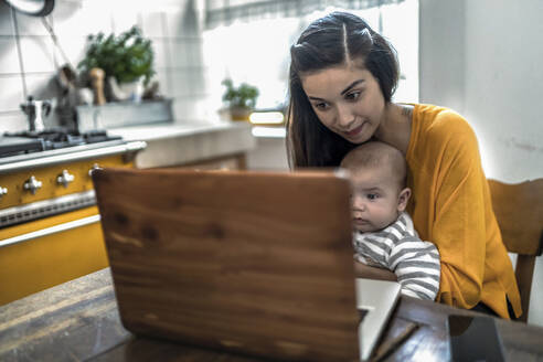 Mother with baby using laptop on kitchen table - RIBF01048