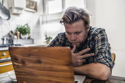 Man using laptop on kitchen table - RIBF01051