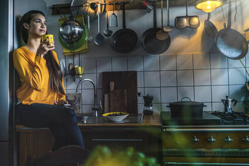 Young woman sitting on kitchen counter at home enjoying a coffee - RIBF01057
