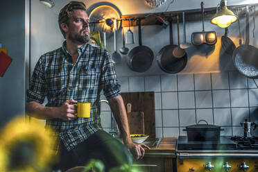 Man in kitchen at home looking sideways - RIBF01060