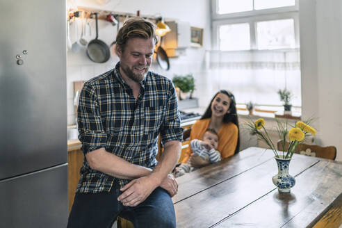 Smiling man with family in kitchen at home - RIBF01066