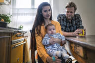 Portrait of family with baby sitting at kitchen table at home - RIBF01069