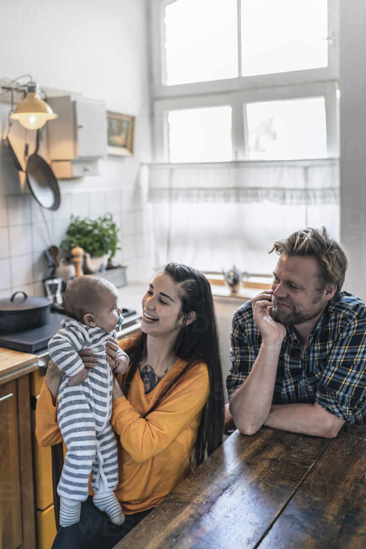 Happy family with baby at kitchen table at home - RIBF01072 - Richárd Bellevue/Westend61