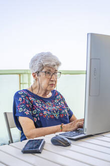 Senior woman using computer on the terrace - DLTSF00110