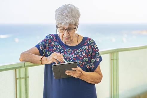 Senior woman using a tablet on a terrace - DLTSF00113