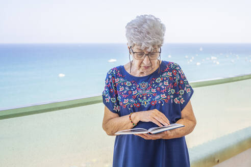 Senior woman reading a book on a terrace - DLTSF00116