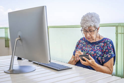 Senior woman using smartphone on the terrace - DLTSF00119