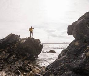 Woman wearing yellow rain jacket standing on rock - UUF18966