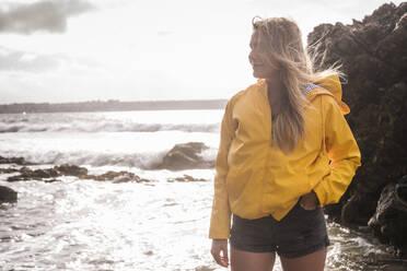 Woman wearing yellow rain jacket standing at the beach - UUF18969