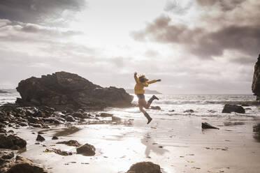 Woman jumping at the beach - UUF18972
