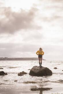 Woman wearing yellow rain jacket standing on rock - UUF18975