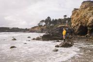 Woman wearing yellow rain jacket standing on rock at the beach - UUF18978