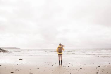 Rear view of woman wearing yellow rain jacket standing at beach - UUF18981