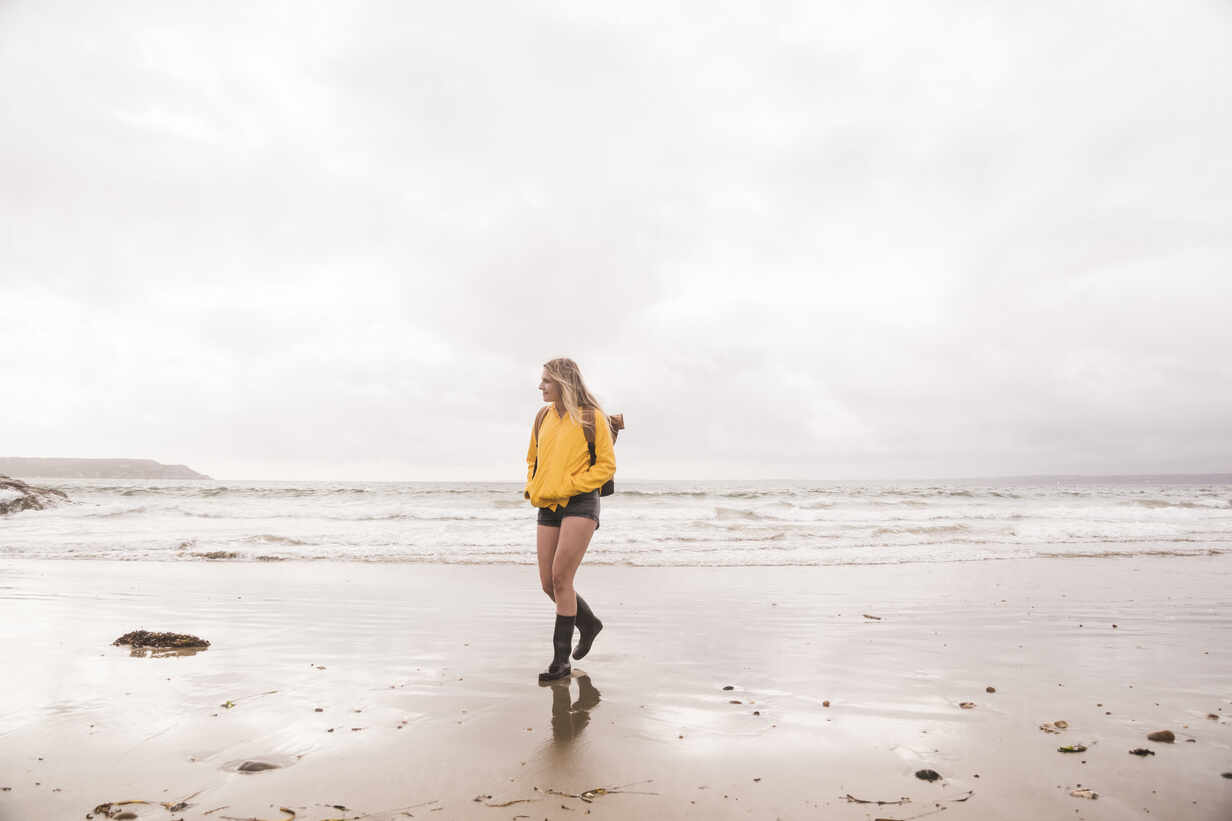 Woman wearing yellow rain jacket walking at the beach - UUF18984 - Uwe Umstätter/Westend61