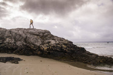 Woman wearing yellow rain jacket standing at rocky beach - UUF18987
