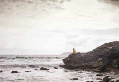Woman wearing yellow rain jacket standing at rocky beach - UUF18993