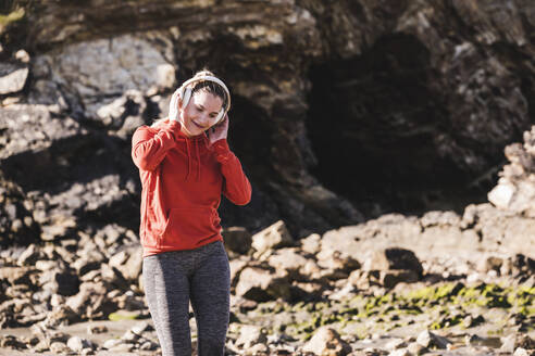 Female jogger at the beach with headphones - UUF19007
