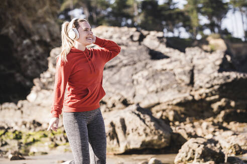Female jogger at the beach with headphones - UUF19010