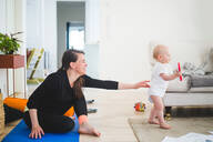 Side view of working mother reaching for daughter while sitting on exercise mat in living room at home - MASF13442