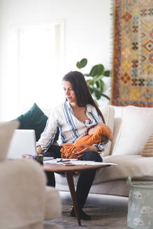 Working mother breastfeeding daughter while using laptop in living room at home office - MASF13490