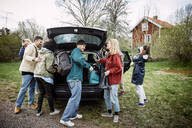 Smiling female and male friends removing luggage from car trunk on road against sky - MASF13646