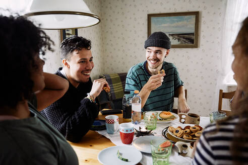Cheerful friends talking while enjoying food in social gathering at home - MASF13655