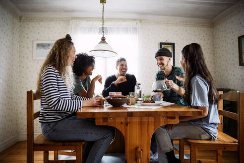 Happy friends talking while enjoying food and drink on table at home - MASF13658