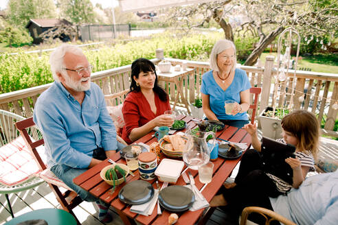 Multi-generational family enjoying food at table in patio - MASF13694