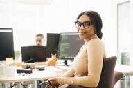 Portrait of female programmer sitting by desk with colleague in background at creative office - MASF13805