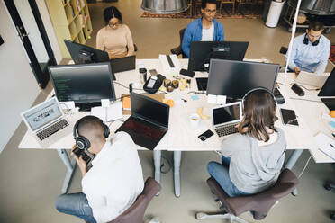 High angle view of IT professionals using technology while sitting at desk in creative office - MASF13838