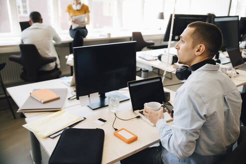 Male computer programmer looking away while sitting at desk in creative office - MASF13856