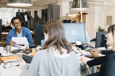Cheerful male and female IT professionals talking while sitting at desk in creative office - MASF13865
