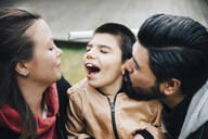 Father kissing happy son looking at his mother in yard - MASF13877