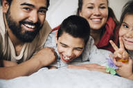 Happy parents with children lying on bed at home - MASF13883