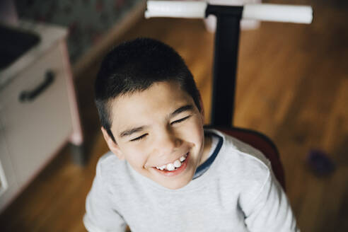 High angle view of happy disabled boy looking away while sitting on wheelchair at home - MASF13889