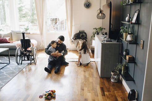 High angle view of father holding autistic son while sitting by daughter on floor at home - MASF13901