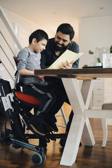 Father teaching autistic son while sitting at table in living room - MASF13922