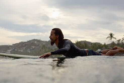 Male surfer paddling out on ocean - FSIF04387
