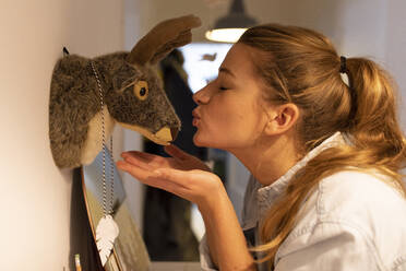 Young woman kissing cuddly tpy hanging at a wall at home - GUSF02475