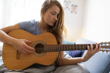 Young woman at home playing guitar with damaged string - GUSF02487