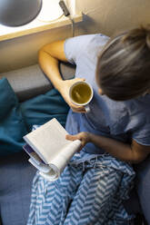 Top view of young woman reading book on couch at home - GUSF02493