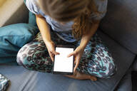 Top view of young woman sitting on couch at home using tablet - GUSF02508