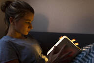 Young woman reading illuminated book on couch at home - GUSF02532