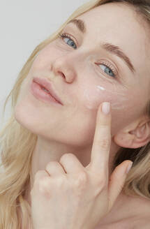 Portrait of young woman applying cream on her face - PGCF00021