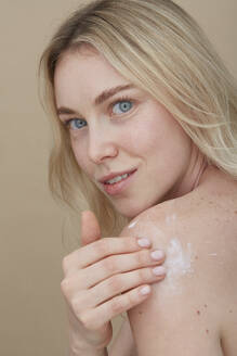 Young woman applying cream on her shoulder - PGCF00024