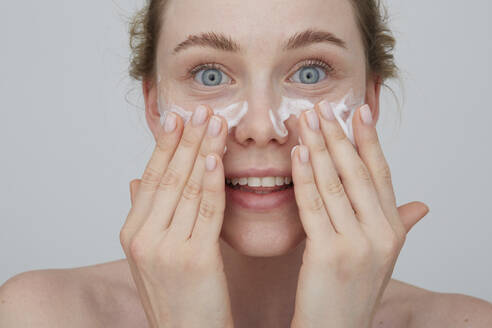 Portrait of blond young woman applying cream on her face - PGCF00027