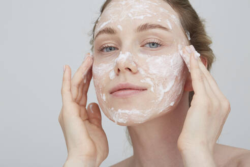 Portrait of blond young woman applying cream on her face - PGCF00030