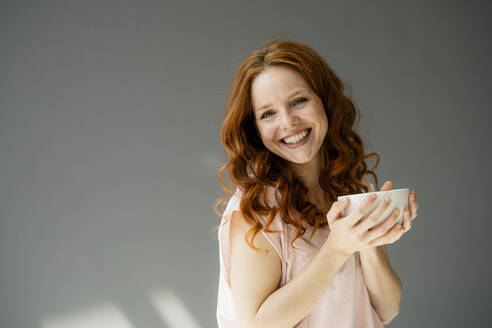Portrait of happy redheaded woman with cereal bowl against grey background - KNSF06491