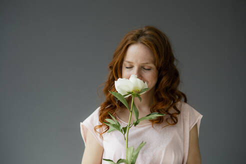 Portrait of redheaded woman smelling white peony - KNSF06494